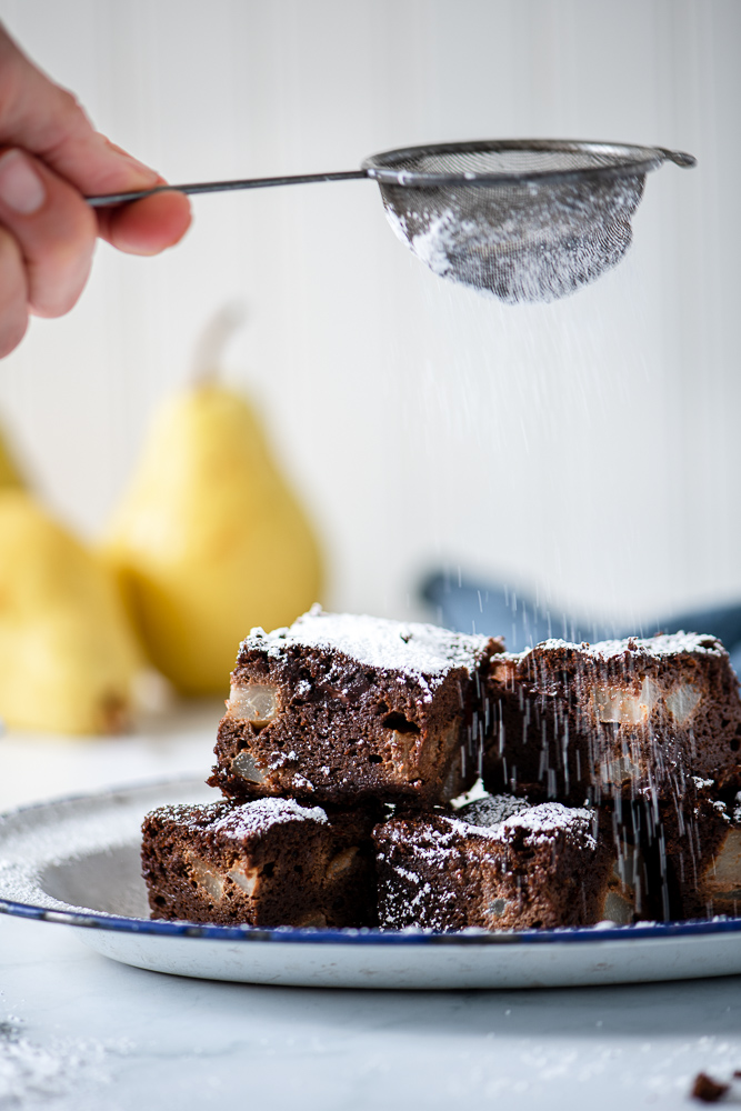 Sprinkling powdered sugar over chocolate pear brownies